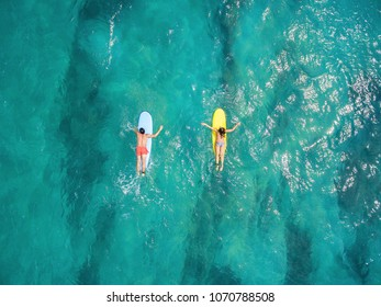 Girl with a guy surfing in the ocean from above