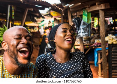 a girl and a guy in a typical african local market laughing