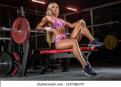 girl in the gym crouches with a barbell, in a beautiful sports uniform, against a dark background.