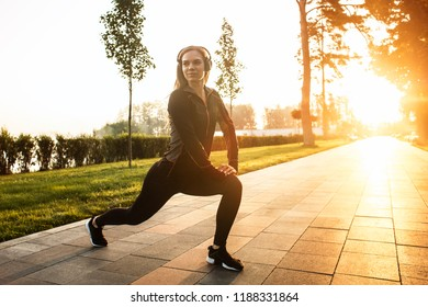 The girl gym in the foggy park. Fitness in the nature. Morning exercise with beautiful, sport woman.Morning gym with headphone. Sport and music.