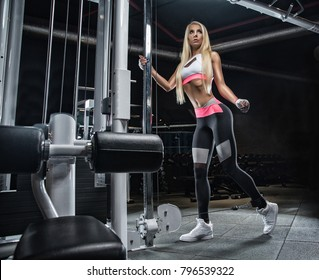 A girl in the gym makes exercises for the development of leg muscles using sports equipment.