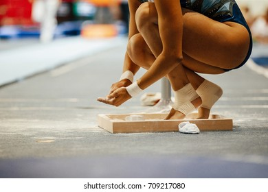 girl gymnast in chalk on hands and feet before performance on balance beam