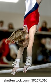 girl gymnast during exercise on bar in gymnastics competitions