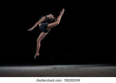 Girl gymnast in a jump with a twine