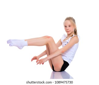 A girl gymnast performs an acrobatic element on the floor. The concept of childhood, sport, healthy lifestyle. Isolated on white background.