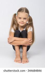 Girl gymnast sitting on the floor hugging his legs