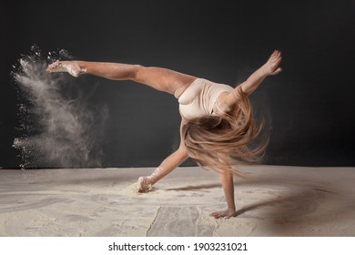 The girl is a gymnast in the studio on a gray background without a face with flying flour. Girl in a beautiful pose, gym, dancing, fitness.