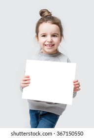 Girl with hair beam holding a white paper, you can place your text. isolated on a gray background