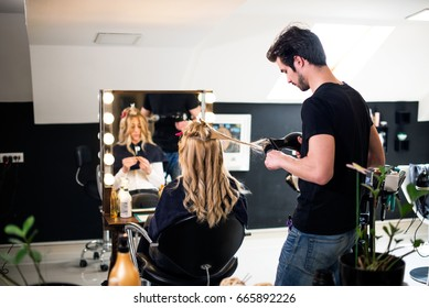 Girl at hair saloon with young male hairdresser