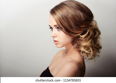 girl with hairdo on white background blond girl with makeup looks away beautiful young girl photo for beauty advertisement