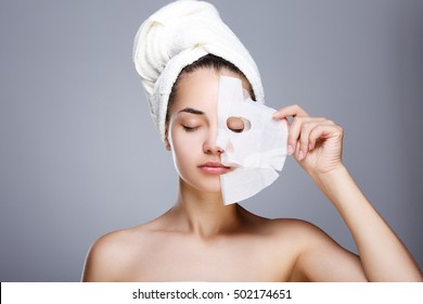 Girl with half rended white mask. Model pulling away mask from her face. Closed eyes. Head and shoulders, studio, indoors