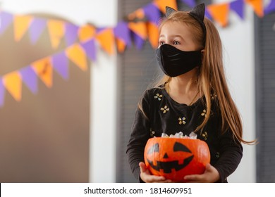 A girl in a Halloween costume with a mask on is holding a pumpkin filled with treats during the covid19 pandemic at a Costume Party.