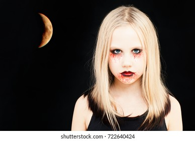 Girl with Halloween Makeup. Portrait of Teen Girl with Artistic Make up and Moon on Black Background