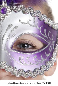 A girl in a halloween or mardi gras mask on a white background