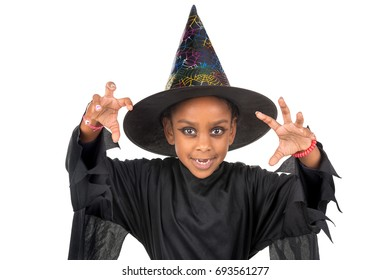 Girl in Halloween witch costume over a white background