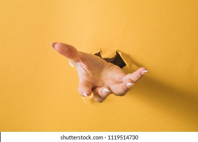 girl hand breaks the yellow paper and shows a gesture.