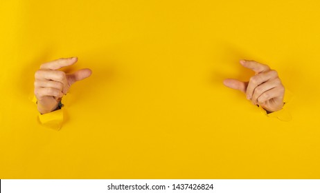 girl hand breaks the yellow paper and shows a gesture with two hands.