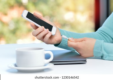 Girl hand connecting charger to smart phone in a table at home with a window in the background