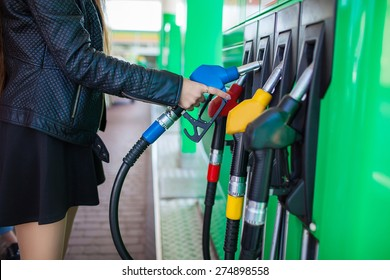 Girl hand with fuel pump at a gas station