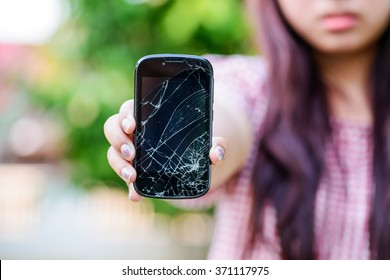 Girl hand holding cracked mobile smartphone