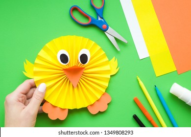 Girl hand holding cute, yellow chick who folded and created from paper. Gift for kids from mother or sister. Colorful application paper, scissors, glue stick and color pens on green desk.