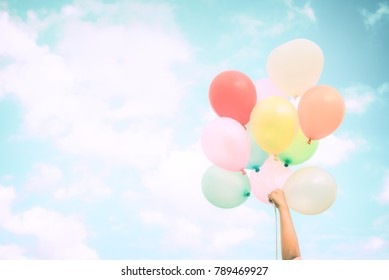 Girl hand holding multi color balloons done with a retro effect, concept of happy birth day in summer and wedding honeymoon party, Vintage color tone style
