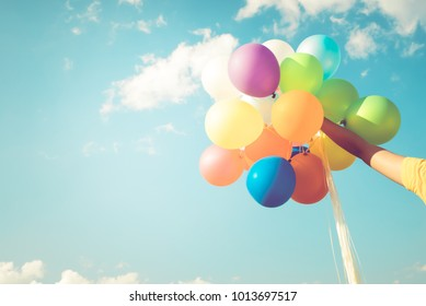 Girl hand holding multicolor balloons done with a retro filter effect, concept of happy birth day in summer and wedding honeymoon party, Vintage color tone style