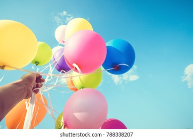 Girl hand holding multicolor balloons done with a retro instagram filter effect, concept of happy birth day in summer and wedding honeymoon party, Vintage color tone style