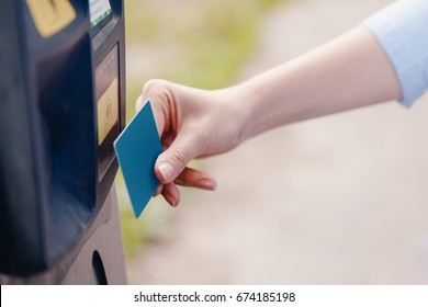 Girl hand inserting ticket into parking machine to pay