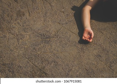 A girl hand lying on the floor. Concept for domestic violence, crime scene, war and child abuse.