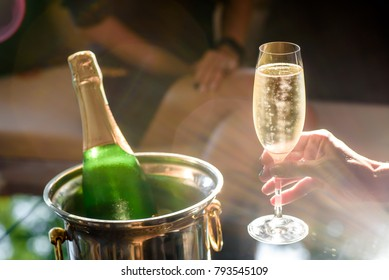 Girl hand with manicure hold champagne glasses on a  beautiful summer terrace. sparkling champagne glasses. close up
