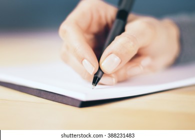 Girl hand with pen and notebook on wooden table, close up