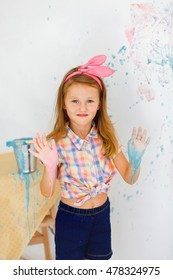 Girl with hand in pink and blue paint near the wall