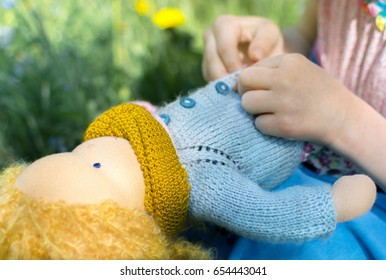 Girl hand playing with hand made textile waldorf doll