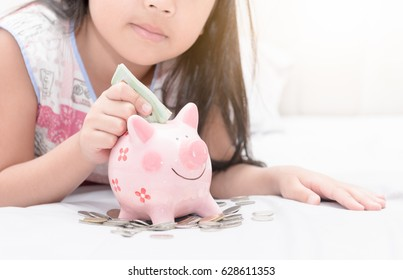 girl hand put money to piggybank on bedroom, concept saving for education.