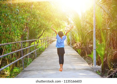 Girl hand  raised up to sky, concept of celebrating freedom. Happy girl in summer forest enjoying nature.