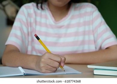 Girl hand writing notebook paper on table, education concept