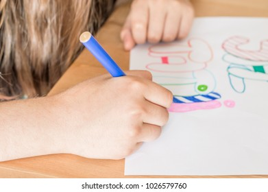 """Girl hand writing """"Summer Vacation"""" in Turkish using colorful felt-tip pen while sitting at table in the classroom."""