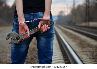 The girl in handcuffs with the adjustable wrench on the railway. The concept of crime prevention with the participation of the railway. Evening photo of the girl's back with handcuffed hands