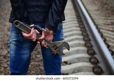 The girl in handcuffs with the adjustable wrench on the railway track background. The concept of crime prevention with the participation of the railway and trains.