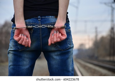 Girl in handcuffs on the background of a railway track. The concept of crime prevention with the participation of the railway. Evening photo of lower half of the body of a girl with handcuffed hands