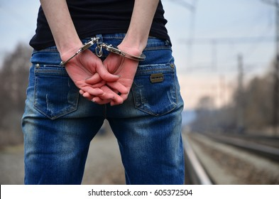 Girl in handcuffs on the background of a railway track. The concept of crime prevention with the participation of the railway. Evening photo of the lower half of the girl's body with handcuffed hands