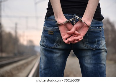 Girl in handcuffs on the background of a railway track. The concept of crime prevention with the participation of the railway and trains. Evening photo of the lower half of the body of a girl