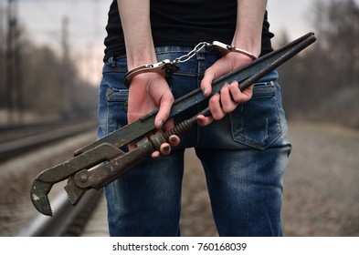 The girl in handcuffs with the pipe wrench on the railway track background. The concept of crime prevention with the participation of the railway and trains.