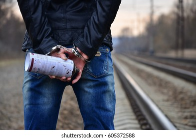 Girl in handcuffs with spraycan on the background of a railway track. The concept of vandalism prevention with the participation of the railway and trains.