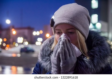 Girl with handkerchief has the flu and running nose winter. In the atmospheric night city