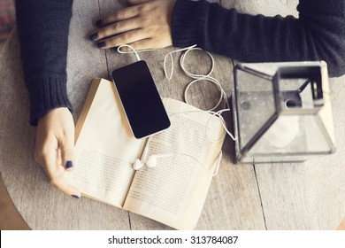 Girl hands with a book and smartphone with headphones
