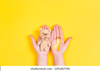 Girl hands holding children's toy with a Childhood Cancer Awareness Yellow Ribbon on yellow background. Childhood Cancer Day February, 15.