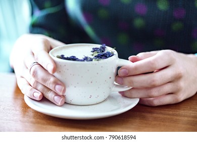 girl hands holding a cup of capuccino