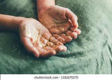 Girl hands holding golden glitter on a green linen fabric. Selective focus.